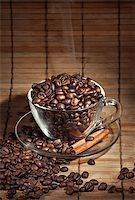 Steaming cup of coffee, cinnamon sticks and a coffee beans Stock Photo - Royalty-Freenull, Code: 400-06911026