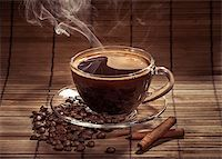 Steaming cup of coffee, cinnamon sticks and a coffee beans Stock Photo - Royalty-Freenull, Code: 400-06911027