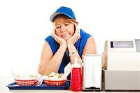 Mature adult fast food worker bored with her job.  Isolated on white. Stock Photo - Royalty-Freenull, Code: 400-06917341