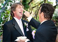 One groom playfully puts wedding cake on his husband's nose at their wedding. Stock Photo - Royalty-Freenull, Code: 400-06926924