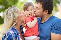 daughter kissing mother - Photo of affectionate parents kissing their small daughter Stock Photo - Royalty-Freenull, Code: 400-06929373
