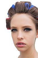 Pretty young model with hair curlers in close up on white background Stock Photo - Royalty-Freenull, Code: 400-06932405