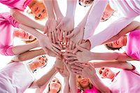 Diverse women smiling in circle wearing pink for breast cancer on white background Stock Photo - Royalty-Freenull, Code: 400-06932893