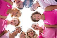 Cheerful women in circle wearing pink for breast cancer and smiling at camera on white background Stock Photo - Royalty-Freenull, Code: 400-06932895