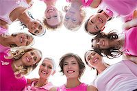 Group of happy women in circle wearing pink for breast cancer on white background Stock Photo - Royalty-Freenull, Code: 400-06932897