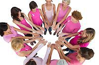 Cheerful women joined in a circle and looking at each other wearing pink for breast cancer on white background Stock Photo - Royalty-Freenull, Code: 400-06932903