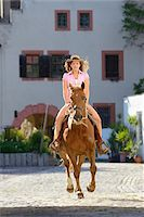 Young attractive woman riding a horse at a castle forecourt, Germany Stock Photo - Premium Rights-Managednull, Code: 700-06936032