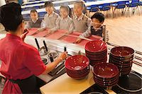 School cafeteria worker serves noodles to students Stock Photo - Premium Royalty-Freenull, Code: 6116-06939451