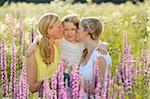 Close-up of a woman with her daughter and her mother in a flower meadow in summer, Bavaria, Germany. Stock Pho