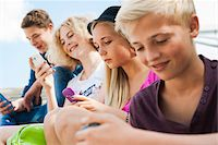Teenagers using Cell Phones Outdoors, Mannheim, Baden-Wurttemberg, Germany Stock Photo - Premium Royalty-Freenull, Code: 600-06939786