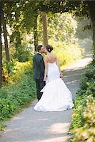 Backview of Bride and Groom kissing and holding hands, walking down pathway outdoors, on Wedding Day Stock Photo - Premium Rights-Managednull, Code: 700-06939704