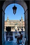 Europe, Spain, Comunidad de Madrid, Madrid, Plaza Mayor, a painter under a arch in the square, Statue of King Philip III in the background