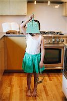 Young girl holding dustpan in front of face, standing in kitchen. Stock Photo - Premium Rights-Managednull, Code: 700-06943757