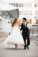 Bride and Groom walking towards camera along walkway in City Park on Wedding Day, Toronto, Ontario, Canada Stock Photo - Premium Rights-Managednull, Code: 700-06960992