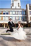 Bride and Groom jumping and having fun posing in City Park on Wedding Day, Toronto, Ontario, Canada