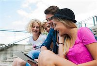 Group of teenagers sitting on stairs outdoors, looking at tablet computer, Germany Stock Photo - Premium Royalty-Freenull, Code: 600-06961020