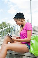 Teenage girl sitting on stairs outdoors, looking at tablet computer, Germany Stock Photo - Premium Royalty-Freenull, Code: 600-06961022
