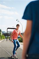 Teenage boy skateboarding on road with back of another boy in foreground, Germany Stock Photo - Premium Royalty-Freenull, Code: 600-06961028