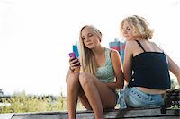 Teenage girls sitting on bench outdoors, looking at cell phone, Germany Stock Photo - Premium Royalty-Freenull, Code: 600-06961042