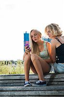 Teenage girls sitting on bench outdoors, looking at cell phone, Germany Stock Photo - Premium Royalty-Freenull, Code: 600-06961043