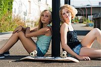 Portrait of teenage girls outdoors with skateboard, looking at camera, sitting on street, Germany Stock Photo - Premium Royalty-Freenull, Code: 600-06961050