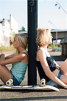 Portrait of teenage girls outdoors with skateboard, sitting on street, Germany Stock Photo - Premium Royalty-Freenull, Code: 600-06961052