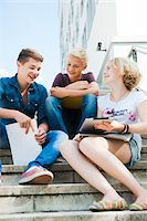 Teenagers sitting on stairs outdoors, talking and looking at tablet computer, Germany Stock Photo - Premium Royalty-Freenull, Code: 600-06961062
