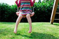 Girl sitting on a swing in backyard Stock Photo - Premium Rights-Managednull, Code: 700-06961790