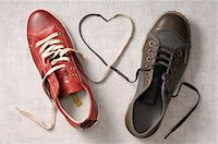 A man's shoe and a woman's shoe with laces tied together in a heart shape Stock Photo - Premium Royalty-Freenull, Code: 600-06961803