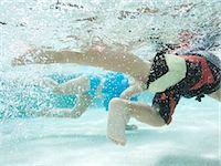 USA, Utah, Orem, Boy (4-5) and girl (2-3) swimming in pool Stock Photo - Premium Royalty-Freenull, Code: 640-06963365