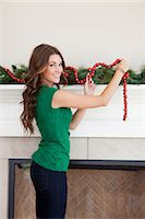 Smiling woman decorating room for Christmas Stock Photo - Premium Royalty-Freenull, Code: 640-06963401