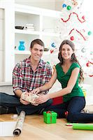 Smiling couple in room packing christmas gifts Stock Photo - Premium Royalty-Freenull, Code: 640-06963407