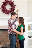 Happy young couple embracing in front of fireplace with Christmas decoration Stock Photo - Premium Royalty-Freenull, Code: 640-06963413