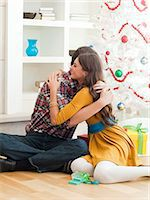 Young couple embracing under Christmas tree Stock Photo - Premium Royalty-Freenull, Code: 640-06963418
