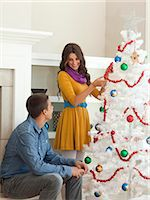 Happy young couple decorating Christmas tree Stock Photo - Premium Royalty-Freenull, Code: 640-06963455