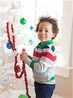 Happy young boy decorating Christmas tree Stock Photo - Premium Royalty-Freenull, Code: 640-06963470