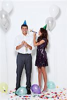 Young couple blowing horns at party Stock Photo - Premium Royalty-Freenull, Code: 640-06963491