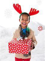 Boy holding a christmas gift. Stock Photo - Premium Royalty-Freenull, Code: 640-06963682