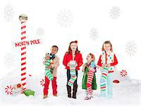 Group of kids (18-23months, 4-5,6-7) standing next to North Pole sign Stock Photo - Premium Royalty-Freenull, Code: 640-06963745