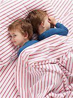 USA, Utah, Orem, Twin boys (2-3) wearing pajamas lying on bed Stock Photo - Premium Royalty-Freenull, Code: 640-06963758