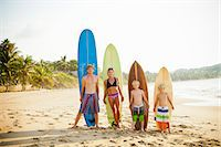 Family standing on beach with surfboards Stock Photo - Premium Royalty-Freenull, Code: 673-06964633
