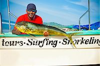 Man with fish on charter fishing boat Stock Photo - Premium Royalty-Freenull, Code: 673-06964762