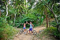 Couple riding bicycles on jungle path Stock Photo - Premium Royalty-Freenull, Code: 673-06964802