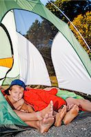 Young boy's face and pairs of feet poking out of tent Stock Photo - Premium Royalty-Freenull, Code: 673-06964814