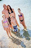 Family standing in shallow water Stock Photo - Premium Royalty-Freenull, Code: 673-06964840