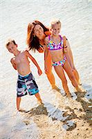 Family standing in shallow water Stock Photo - Premium Royalty-Freenull, Code: 673-06964841