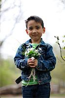 Smiling boy holding flowers Stock Photo - Premium Royalty-Freenull, Code: 6102-06965586