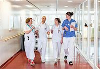 Team of doctors communicating while walking in hospital corridor Stock Photo - Premium Royalty-Freenull, Code: 698-06966362