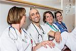 Happy male doctor and female colleagues leaning together on wall in hospital Stock Photo - Premium Royalty-Freenull, Code: 698-06966365