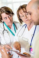 Senior female doctor discussing over digital tablet with colleagues in hospital Stock Photo - Premium Royalty-Freenull, Code: 698-06966372